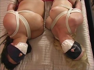 Two tape gagged blindfolded crotch rope bondage