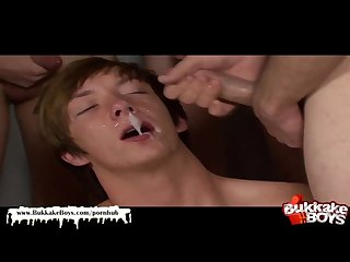 Twink cum whore is on his knees getting creamed in a huge bukkake gangbang