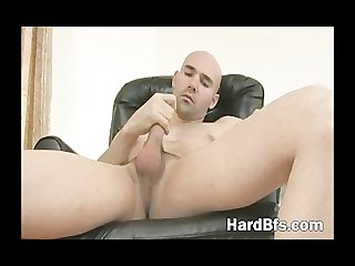 Good looking man sits on the couch and plays with his white dick