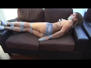 Girl in sneakers and jeans shorts tape tied and sock gagged