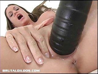 Petite brunette stretching her pussy with a thick dildo