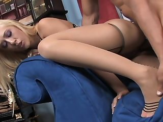 Busty blonde in thigh high seamed stockings giving a footjob and fucking