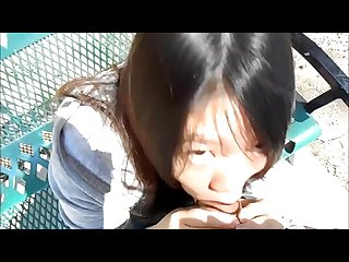Asian woman blowing guys in the park in broad day light