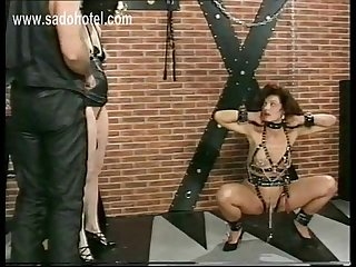 Tied beautiful slave with large metal clamps with heavy weight on her pussy lips is spanked