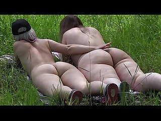 Voyeur outdoors peeps at two naked lesbians. Nudists with big asses sunbathe and enjoy..