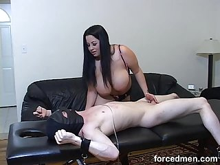 Mistress smothers slave with her big tits and rubs his cock afterwards
