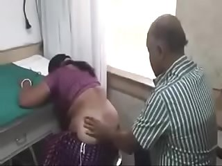 Doctor illustrating injection process by giving it in desi aunty s bum