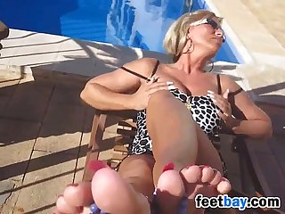 Milf tans and teases her feet outside