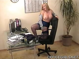 Busty blonde secretary in blue stockings at the office